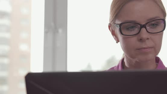 Cover Image for Portrait of Smiling Woman Wearing Glasses Working at Home with a Laptop