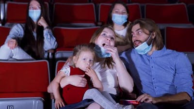 Family in masks in movie theater