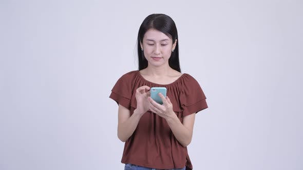 Thumbnail for Happy Beautiful Asian Woman Using Phone and Getting Good News