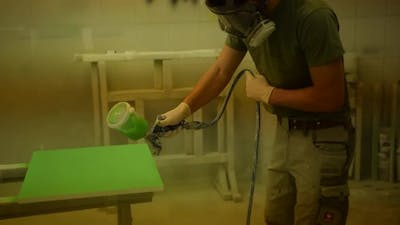 Painter Coloring a Piece of Wood with Green Color and Electric Spray Paint Machine