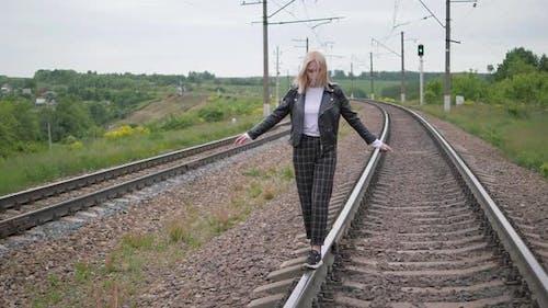 Young Woman Walks on the Rail of the Railway Tracks