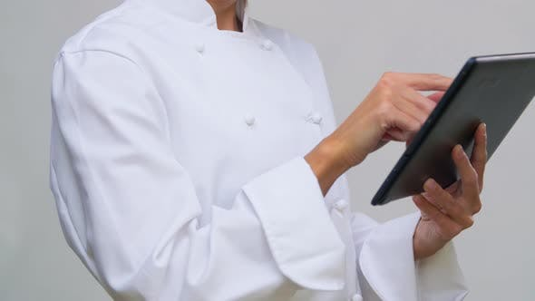 Smiling Female Chef in Toque with Tablet Computer