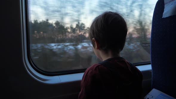Thumbnail for Little boy traveling in train looking outside the window. School holidays ahead.