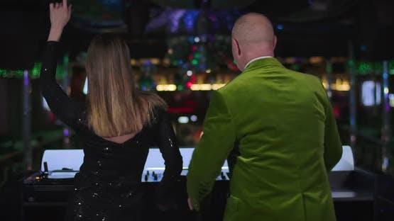 Rückansicht von jungen attraktiven kaukasischen Frau und Senior fröhlichen Mann tanzen auf der Bühne im Nachtclub