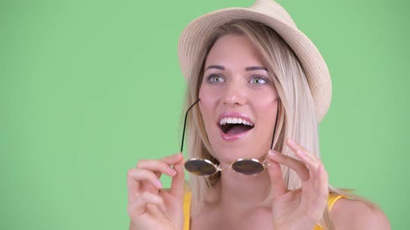 Thumbnail for Face of Happy Young Blonde Tourist Woman Looking Surprised