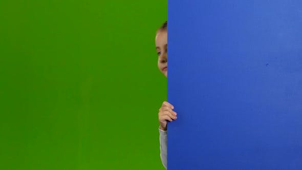 Thumbnail for Child Looks Out From Behind a Blue Blank Board and Waves. Green Screen