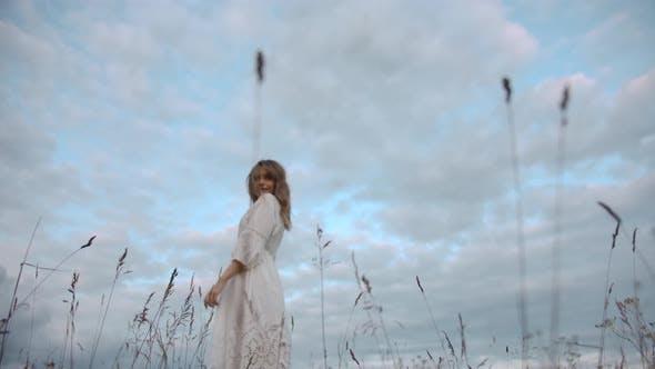 Thumbnail for Elegant Romantic Female in White Dress Strolling in Grass