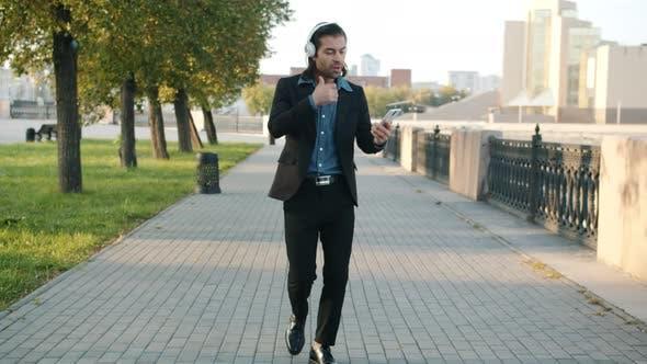Joyful Businessman Walking in City Wearing Headphones Using Smartphone Dancing Having Fun