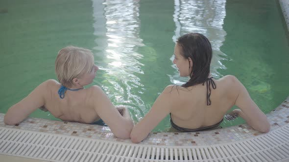 Thumbnail for Top View of Positive Caucasian Women Resting at Poolside and Talking. Back View of Young Beautiful