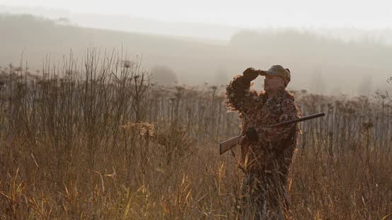 Thumbnail for Hunter with Rifle Standing in the Field and Looking Around, Foggy Autumn Morning, Soft Sun Light