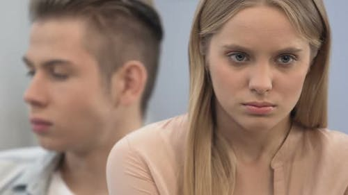 Emotionally immature high-school couple sulking, crisis in relations, conflict