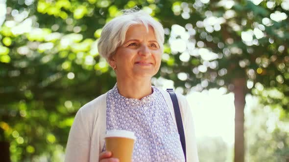 Thumbnail for Senior Woman Walks Along Park and Drinks Coffee 8
