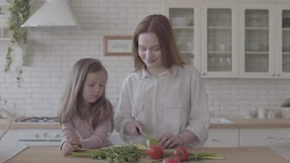Thumbnail for Portrait Pretty Young Smiling Woman Cooking Salad at the Table, Cutting Zucchini. Little Girl
