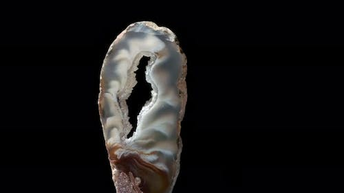 Agate with Quartz. Agate Rotates Around Its Axis on a Black Background.
