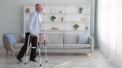 Impaired Mature Male Walking With Disability Frame At Home