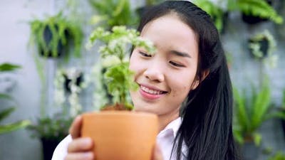 woman happy looking a plant