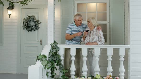 Senior Elderly Caucasian Couple Drinking Wine, Making Kiss in Porch at Home. Enjoying Life Together