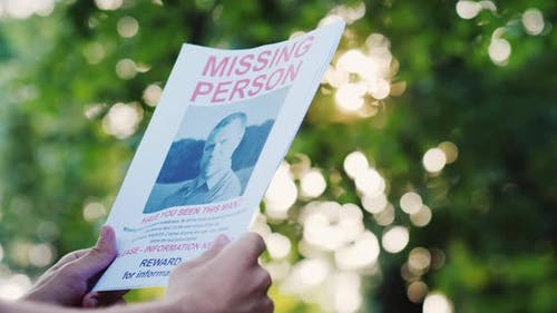 Man Holding a Flyer with the Announcement of the Missing Man