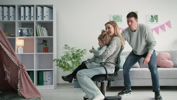 Family Fun Joyful Man Has Fun Rolling Young Woman and Daughter on Chair While Hanging Out Together