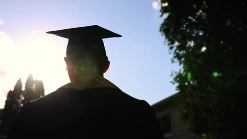 Close Up Rear View of the University Graduates Student at Silhouette Sunset