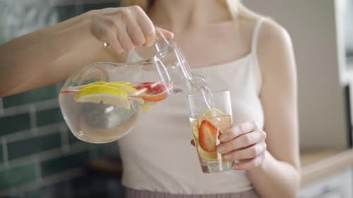 Close Up of Slim Woman with Fruit Detox Water in Glass Bottle