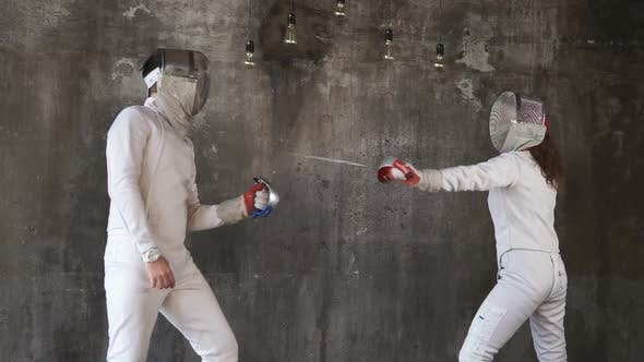 Two Sportsmen Are Engaged in Fencing in the Sports Center, the Pair Is Trained