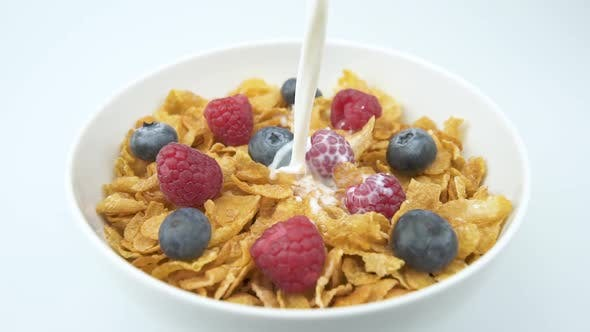 Pouring Milk Into Corn Flakes With Raspberry In A Bowl