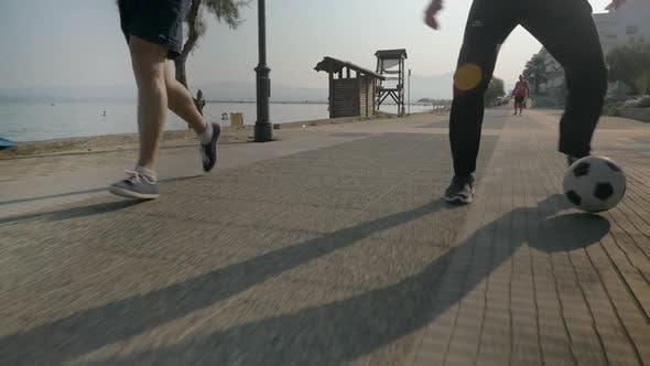 Two Men Dribbling Soccer Ball on the Footwalk