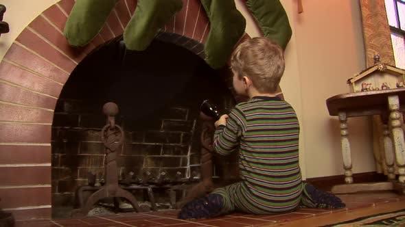 Kleinkind im Pyjamas auf der Suche nach Santa im Kamin zu Weihnachten