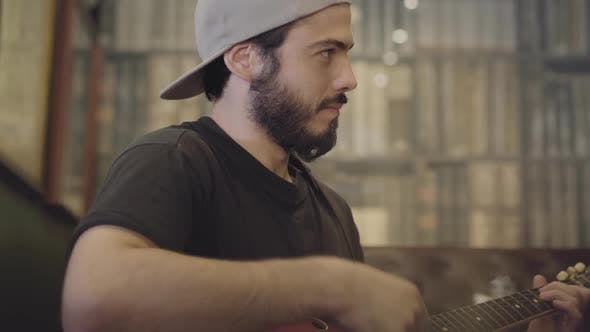 Cover Image for Skill Young Bearded Man Playing Guitar in the Bar Looking at Camera