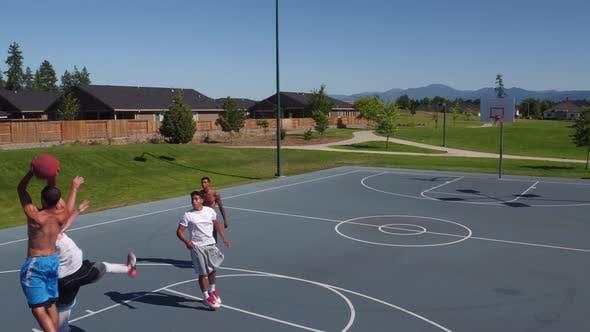 Thumbnail for Friends playing basketball at park, high angle shot