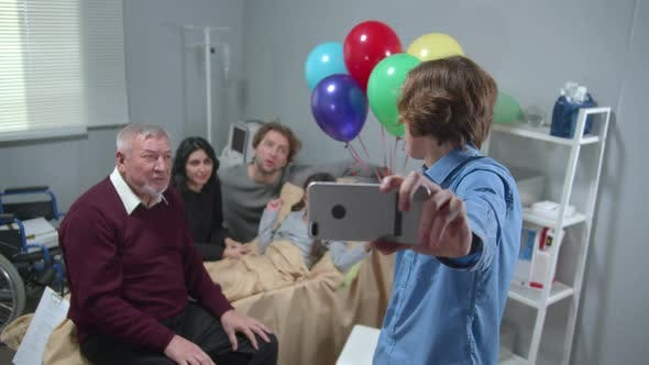 Cover Image for Relatives Visit Girl Who Lie on the Bed in the Hospital, Boy Take a Photo