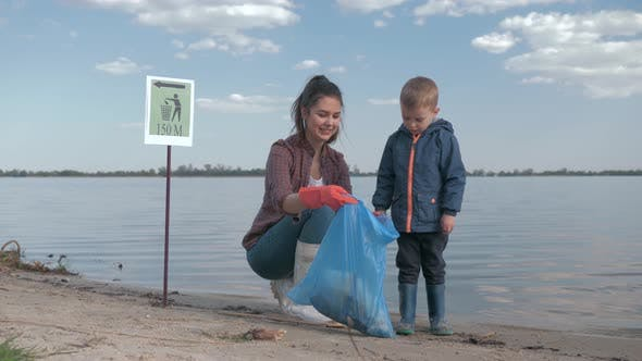 Thumbnail for Environmental Volunteers, Young Woman Is Consider with Kid Boy How Much Rubbish Is Collected in