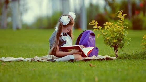 School Girl Reading Book on Lawn