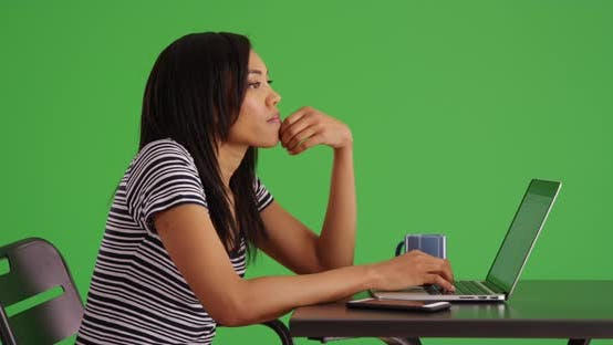 Thumbnail for Side view of black woman working on laptop computer at table on greenscreen