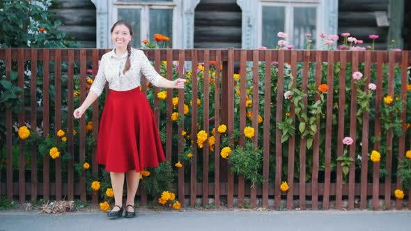 Thumbnail for A Young Woman in Long Red Skirt Dancing By the Fence on the Street in the Village