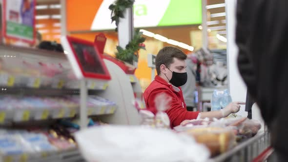 Male Salesman Cashier in Supermarket Scans Goods at Checkout