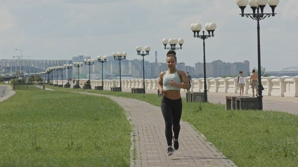 Thumbnail for Young woman runner running on city bridge road