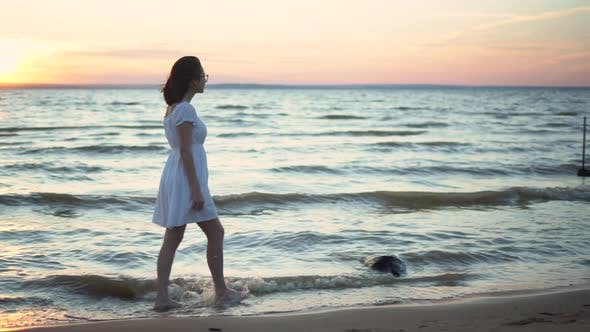 Thumbnail for Attractive Young Woman Walks Along the Sea Beach at Sunset. A Girl in a White Dress Walks Barefoot