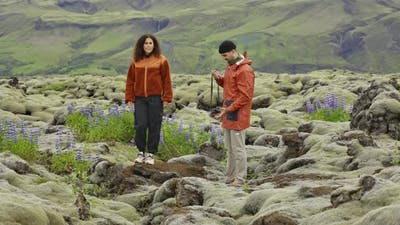 Hiking Couple In Mossy Landscape With Wildflowers