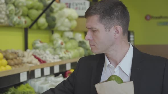 Thumbnail for Close-up of Confident Adult Caucasian Man Choosing Pomelo in Grocery, Putting Citrus Fruits Into