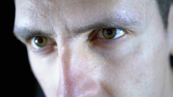 Thumbnail for Close-up of the Eyes and Face of a Young Man Working at a Computer on a Black Background