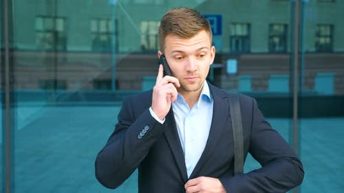 Young Businessman Talking on Phone Near Office and Celebrating Achievement