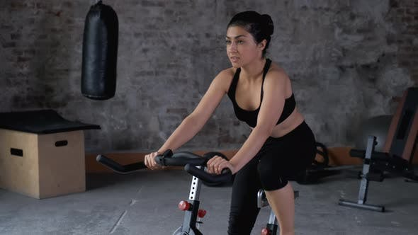 A beautiful athletic young brunette woman in sportswear trains on a sycle in the gym