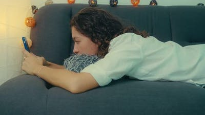 Young Woman is Using Smart Phone and Lying on Couch Leisurely in Living Room
