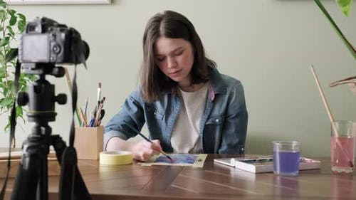 Artist teenage girl, draws and records on video camera for his blog. Slider tracking shot
