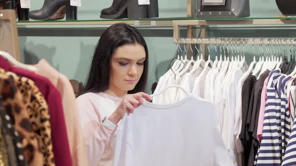 Thumbnail for Beautiful Young Woman Choosing T-shirt To Buy at the Clothing Store