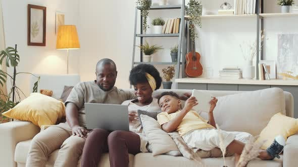 Thumbnail for Happy Afro-American Family Watching Video on Laptop on Sofa