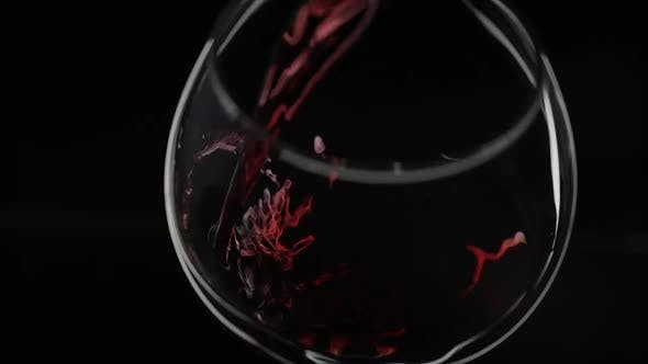 Rose Wine. Red Wine Pour in Wine Glass Over Black Background. Slow Motion