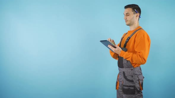 Yonug Worker with Tablet in Studio Blackground with Copy Space